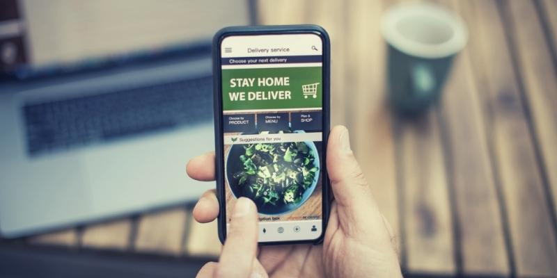Photo of a shopper using a mobile shopping app that now enables them to get a home delivery.