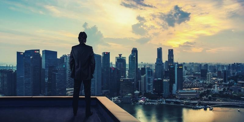 A CEO looking out over the city from his office rooftop contemplating his shared vision for transformation.